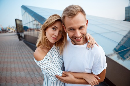 rejoicing: Young beautiful couple smiling, rejoicing, embracing, walking around city