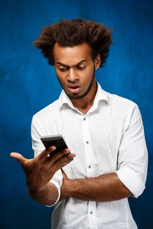 Displeased young handsome african man in white shirt looking at phone over blue background. Copy space.