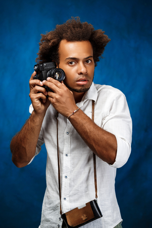 Young handsome african man in white shirt holding old camera, posing over blue background. Copy space. Stock Photo