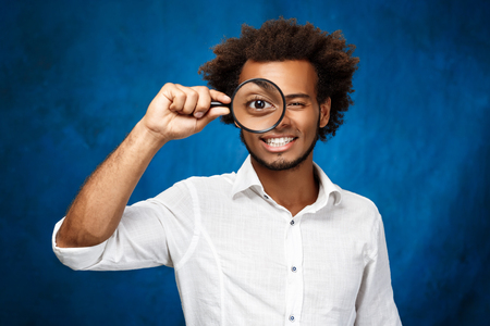 Young handsome african man in white shirt posing with magnifier over blue background. Copy space. Stock Photo