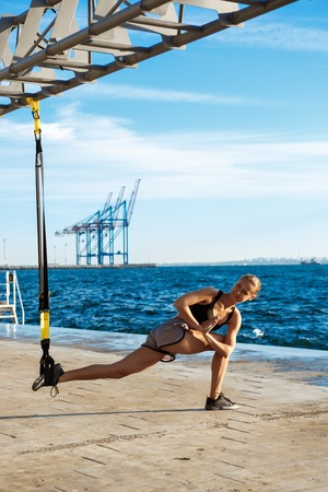 Young beautiful sportive girl training with trx near sea.