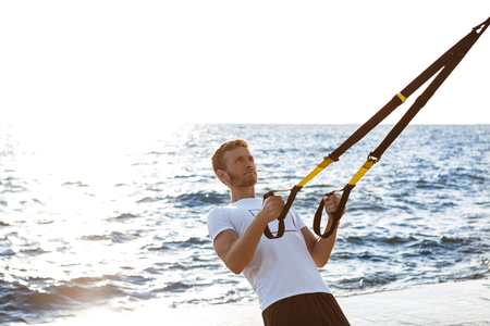 Young sportive handsome man training with trx near sea.