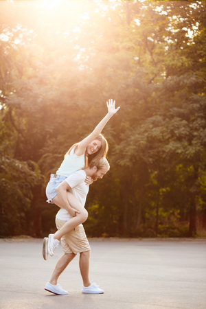 rejoicing: Young beautiful couple resting, walking in park, smiling, rejoicing