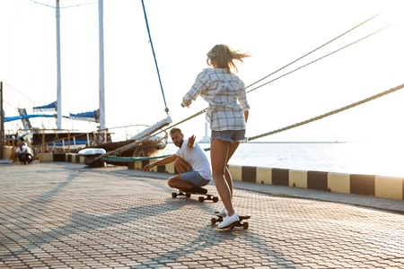 Young beautiful couple walking at seaside, skateboarding. Outdoor background. Stock Photo