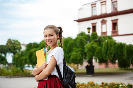 Young beautiful female student smiling, holding folders outdoors, park background.