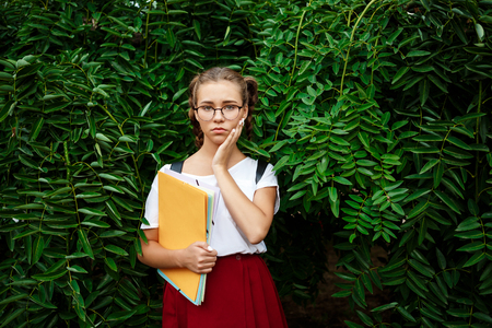Upset young beautiful female student  holding folders outdoors, park background.