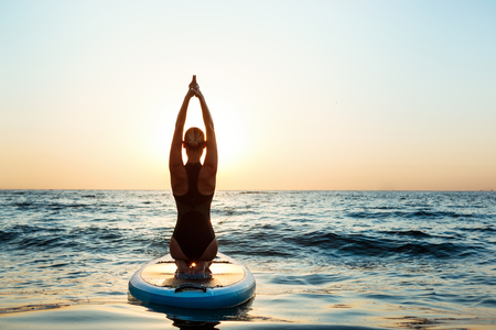 pleasures: Silhouette of young beautiful girl practicing yoga on surfboard in sea at sunrise. Stock Photo