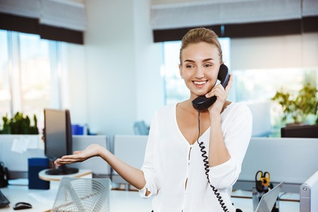 biz: Young beautiful successful businesswoman smiling, speaking on phone, office background.