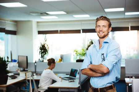 sincere girl: Young handsome successful businessman smiling, posing with crossed arms, office background.
