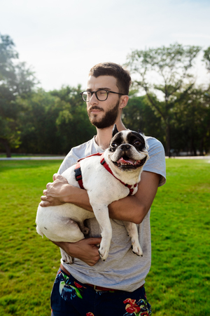 Handsome man holding French bulldog, walking in park. Outdoor background.