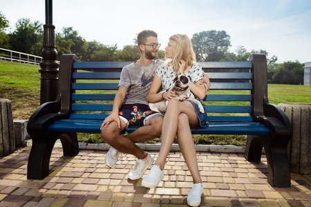 Beautiful couple smiling, walking, sitting with French bulldog on bench in park. Outdoor background.