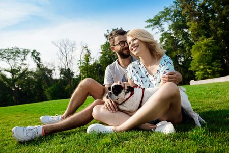grass beautiful: Beautiful couple smiling, sitting on grass with French bulldog in park. Outdoor background.