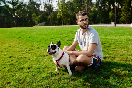 Handsome man sitting, playing with french bulldog on grass in park. Outdoor background.