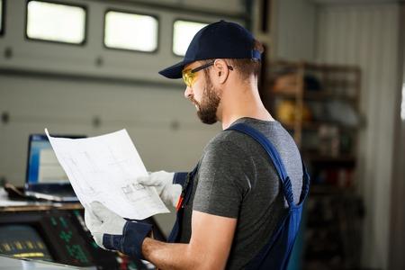 overol: Retrato de los trabajadores en overoles, acero industrial fondo fábrica. Foto de archivo