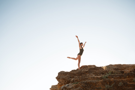 Young beautiful ballerina dancing, posing on rock at beach, sea background.