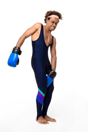 Young handsome sportive african man trying take off boxing gloves over white background. Copy space. Stock Photo