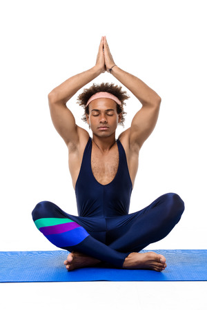 Young handsome sportive african man meditating, sitting on karemat over white background. Copy space.