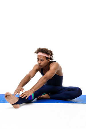 Young handsome sportive african man stretching, sitting on karemat over white background. Copy space.