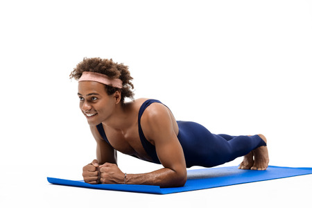 Young handsome sportive african man training on karemat over white background. Copy space. Stock Photo