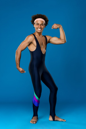 showing muscles: Young handsome sportive african man smiling, posing, showing muscles over blue background. Copy space. Stock Photo