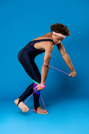 Young handsome sportive african man fooling, posing with skipping rope over blue background. Copy space.