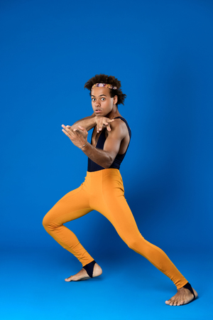 Young handsome sportive african man training martial poses over blue background. Copy space.