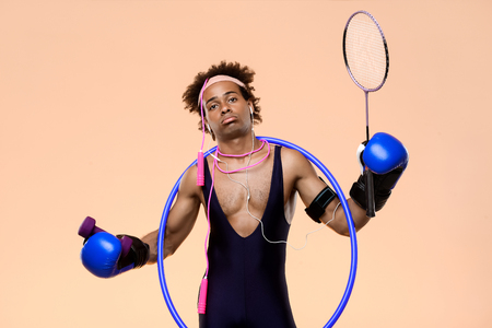 Young handsome sportive african man posing with boxing gloves, hoop, skipping rope, racket over orange background. Copy space.
