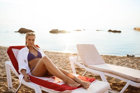 Beautiful blonde girl in swimwear lying on chaise near sea  at sunrise. Copy space. Stock Photo