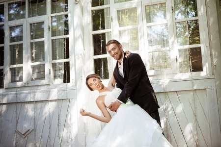 dressy: Young beautiful dressy newlyweds smiling, fooling, dancing outdoors. Copy space
