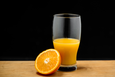 Glass of juice and half of orange on wooden desk over black background. Copy space. Stock Photo