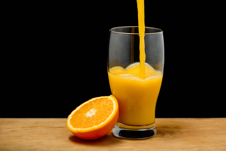 Pouring orange juice into glass over black background. Copy space.