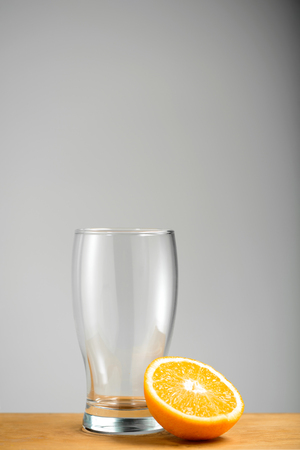 Empty glass with half orange on wooden desk over grey background. Copy space. Stock Photo