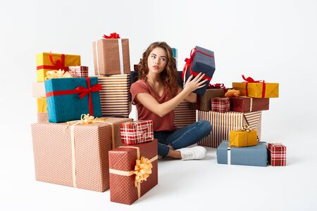 Young beautiful curly girl sitting on floor among gift boxes guessing what is inside  Copy space