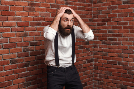 Surprised young handsome man in suit with suspenders over brick background. Copy space.