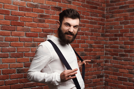 Young handsome man in suit with suspenders posing over brick background. Copy space.