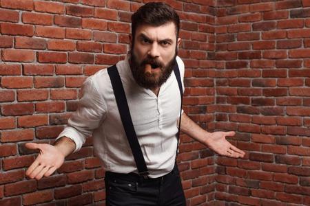 hombre fumando puro: rabia brutal hombre joven y guapo fumar cigarro sobre el fondo de ladrillo. Espacio de la copia.