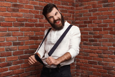 Young handsome man in suit with suspenders rejoicing posing over brick background. Copy space.