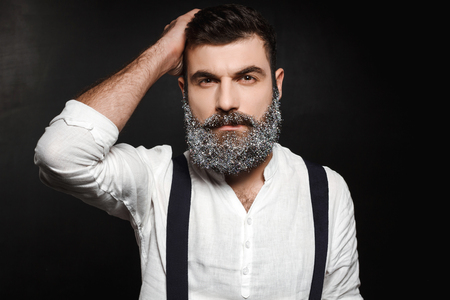 Portrait of young handsome man with beard in snow looking at camera over black background. Copy space.
