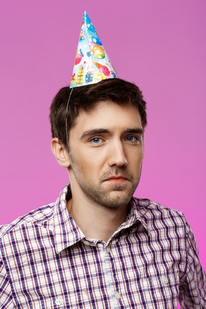 Resentful young handsome man posing over purple background. Birthday party. Copy space. Stock Photo