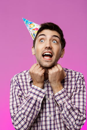 Handsome man trying to take off birthday hat over purple background. Copy space. Stock Photo