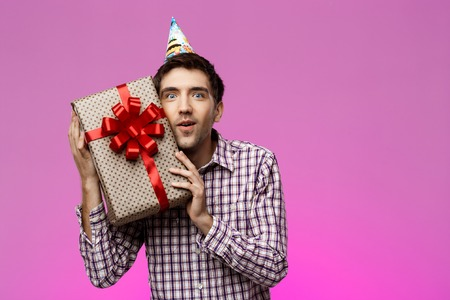 Happy young handsome man holding birthday gift in box over purple background. Copy space.