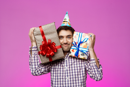 Happy Young Man Holding Birthday Gifts In Boxes Over Purple Background Stock Photo Picture And Royalty Free Image 68100624