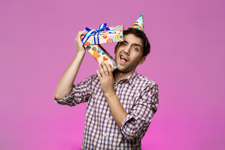 Young handsome man escape from birthday box over purple background. Copy space. Stock Photo