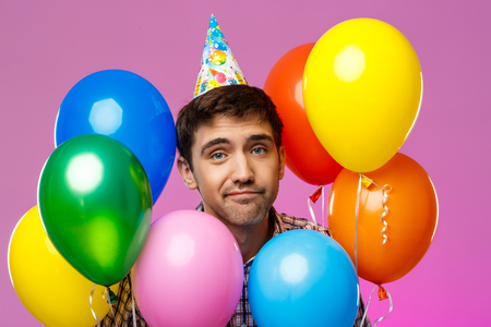 Upset young handsome man celebrating birthday, holding colorful baloons over purple background. Copy space.