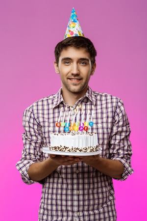 Young handsome man smiling, holding birthday cake over purple background. Copy space. Reklamní fotografie