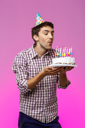 Young handsome man blowing out candles on birthday cake over purple background. Copy space.