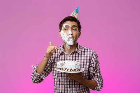 Young handsome man with cake on face over purple background. Birthday party. Copy space. Stock Photo