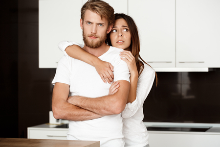 Sad young handsome man taking offense at his girlfriend regreting embracing him. Kitchen background. Stock Photo