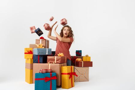 Young surprised beautiful curly girl among lying and falling gift boxes Isolated Copy space Stock Photo
