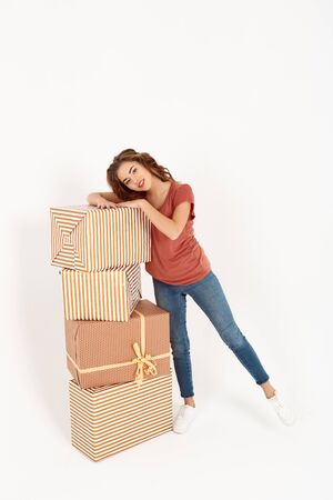 Cheerful young beautiful girl standing next to stack of big gift boxes Isolated Copy space Stock Photo
